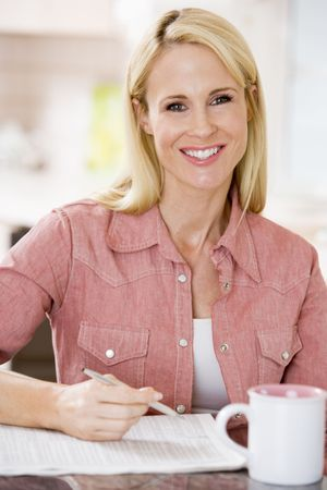 Woman in kitchen with newspaper and coffee smiling photo