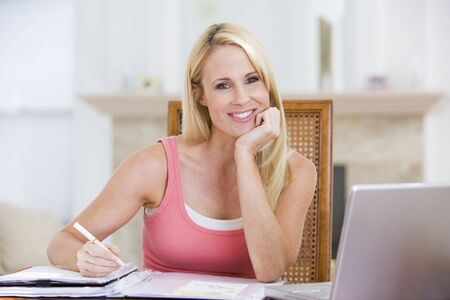 Woman in dining room with laptop smiling photo