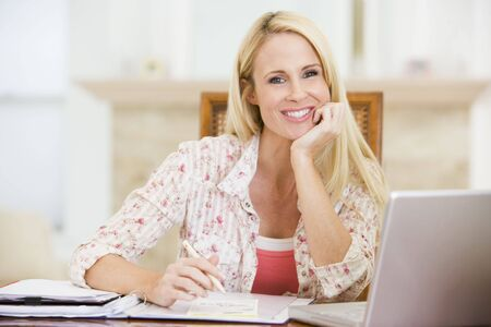 Woman in dining room with laptop smiling Stock Photo - 3487810