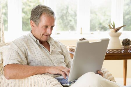 Man in living room with laptop photo