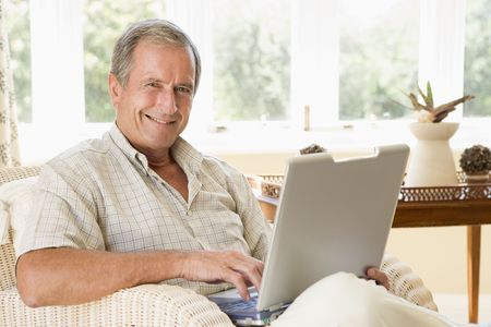 Man in living room with laptop smiling Stock Photo - 3484723