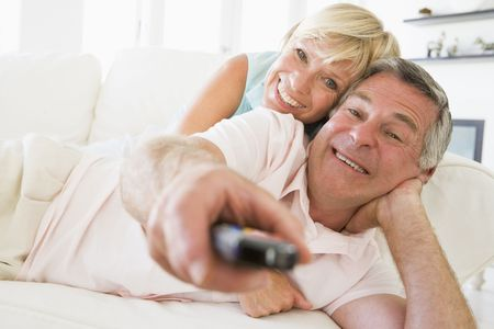 Couple in living room using remote control smiling photo