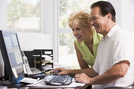 Couple in home office at computer smiling photo