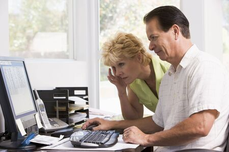 Couple in home office at computer frowning photo