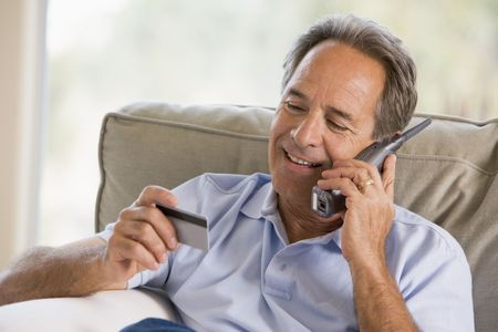 cordless phone: Man indoors using telephone and looking at credit card smiling