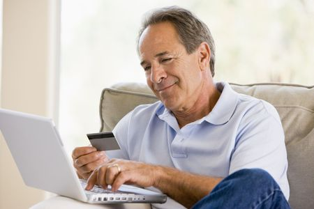 Man in living room with laptop and credit card smiling Stock Photo - 3485185