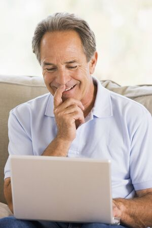 silver surfer: Man in living room with laptop smiling