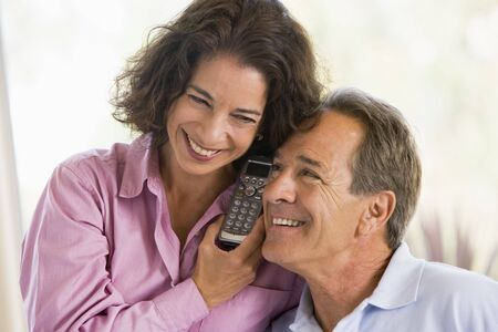 talking telephone: Couple indoors using telephone smiling