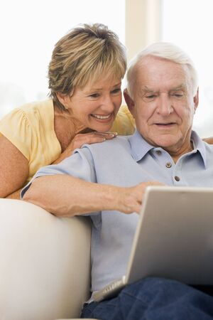 silver surfer: Couple in living room with laptop smiling