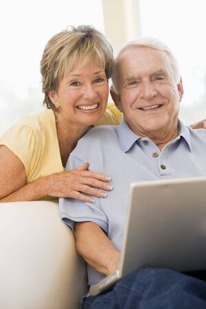 Couple in living room with laptop smiling photo