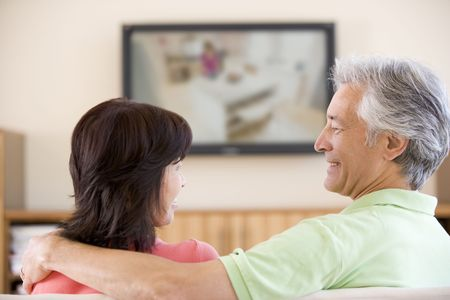 Couple watching television smiling photo