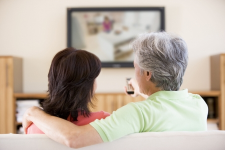 Couple watching television using remote control photo