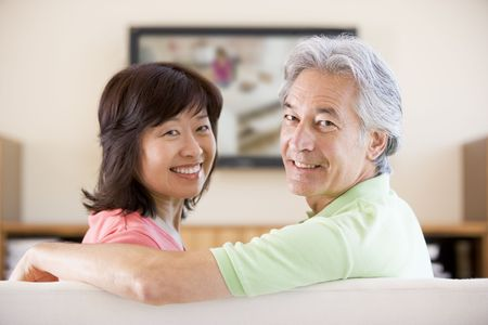 Couple watching television smiling Stock Photo - 3484606