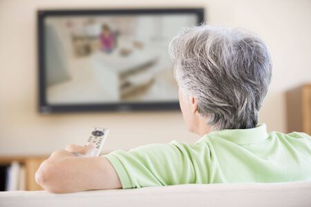 Man watching television using remote control Stock Photo - 3484732