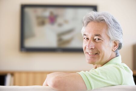 hombre sentado: El hombre sonriente viendo la televisi�n