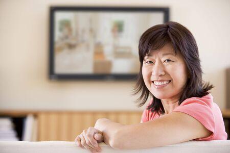 one senior adult woman: La mujer viendo la televisi�n sonriendo