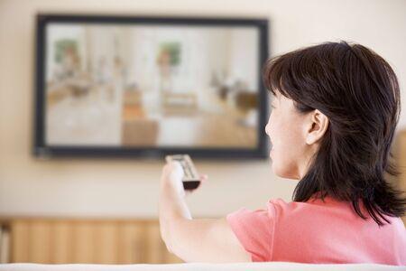 mujer viendo tv: Mujer viendo la televisi�n usando el control remoto