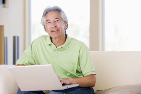 Man in living room with laptop smiling Stock Photo - 3482845