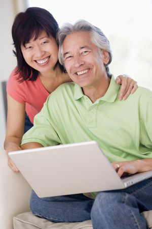 mixed race couple: Couple in living room with laptop smiling