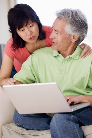 Couple in living room with laptop smiling Stock Photo - 3485679
