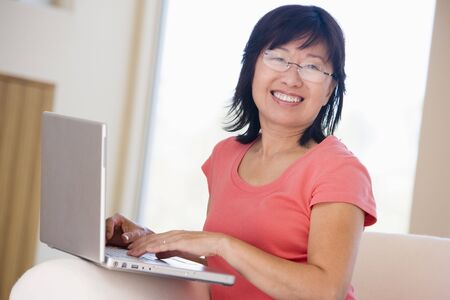Woman in living room with laptop smiling photo
