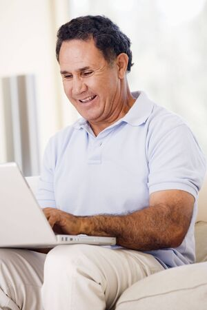 Man in living room with laptop smiling Stock Photo