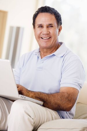 hispanic women: Man in living room with laptop smiling
