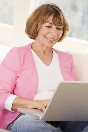 silver surfer: Woman in living room with laptop smiling