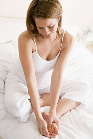 Pregnant woman sitting in bed smiling and rubbing feet photo