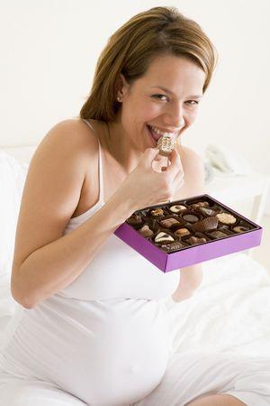 mujeres sentadas: Mujer embarazada en la cama comiendo chocolate sonriente Foto de archivo