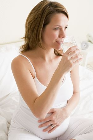 Pregnant woman sitting in bedroom with glass of water smiling photo