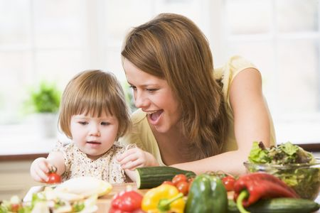 Mother and daughter in kitchen making a salad smiling photo