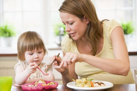 Pregnant mother in kitchen eating chicken and vegetables helping daughter eat photo