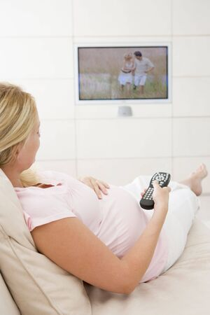pregnant relaxing on sofa: Pregnant woman watching television using remote control