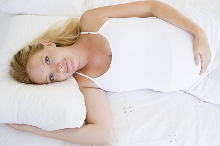 Pregnant woman lying in bed smiling Stock Photo - 3485787