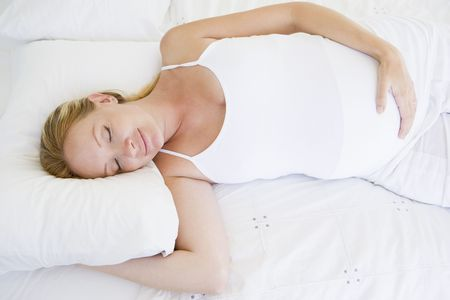 Pregnant woman lying in bed sleeping Stock Photo - 3485783