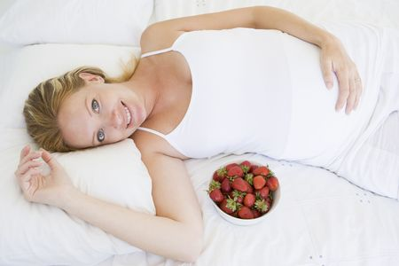 Pregnant woman lying in bed with bowl of strawberries smiling Stock Photo - 3485839