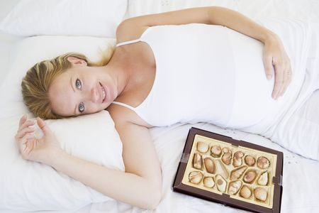 Pregnant woman lying in bed with chocolates smiling photo