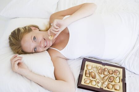 Pregnant woman lying in bed with chocolates smiling Stock Photo - 3486072