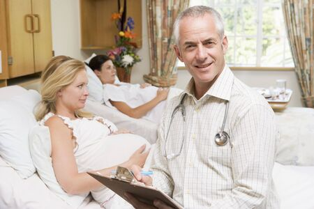 maternity ward: Doctor sitting by pregnant women holding chart and smiling