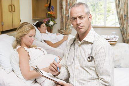Doctor sitting by pregnant women holding chart Stock Photo - 3487134