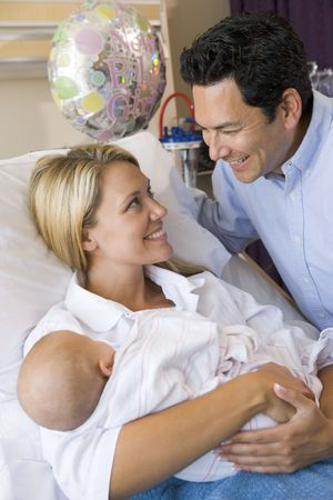 New mother with baby and husband in hospital smiling photo