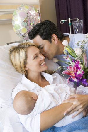 New mother with baby and husband in hospital smiling Stock Photo - 3487441