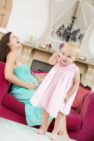 pregnant relaxing on sofa: Pregnant mother holding belly in pain with daughter pointing in foreground Stock Photo
