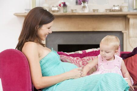 baby on chair: Pregnant mother with daughter in living room touching belly and smiling