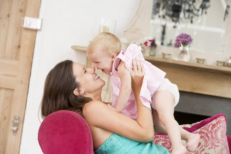 Pregnant mother in living room holding daughter and laughing photo