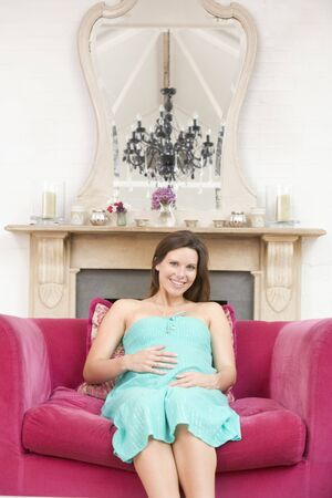 Pregnant woman sitting in living room smiling photo