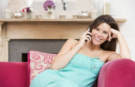 Pregnant woman in living room talking on telephone and smiling photo