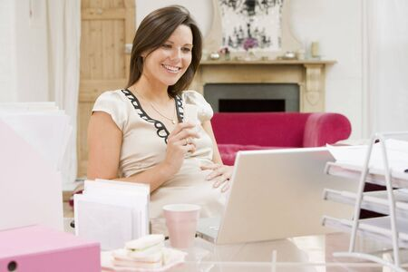 maternity leave: Pregnant woman in home office with laptop eating and smiling