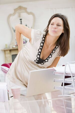 Pregnant woman in home office with a sore back photo